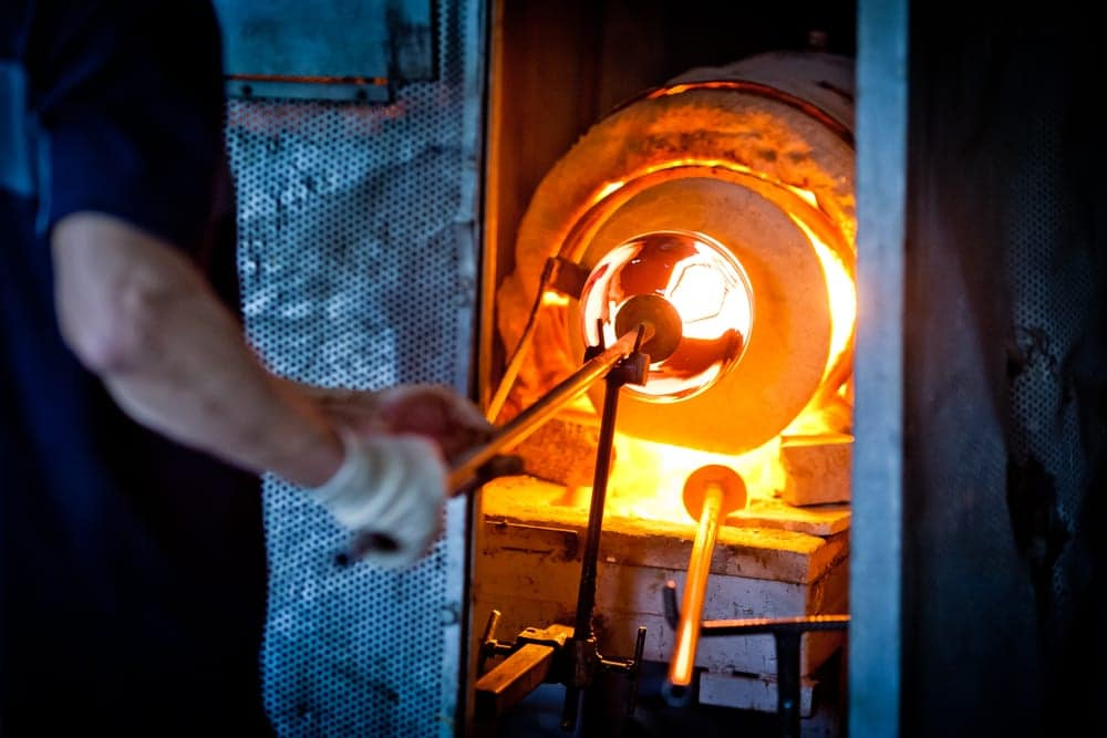 Professional glass blower creating art in a kiln