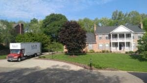 Red Krupp moving truck in front of nice house