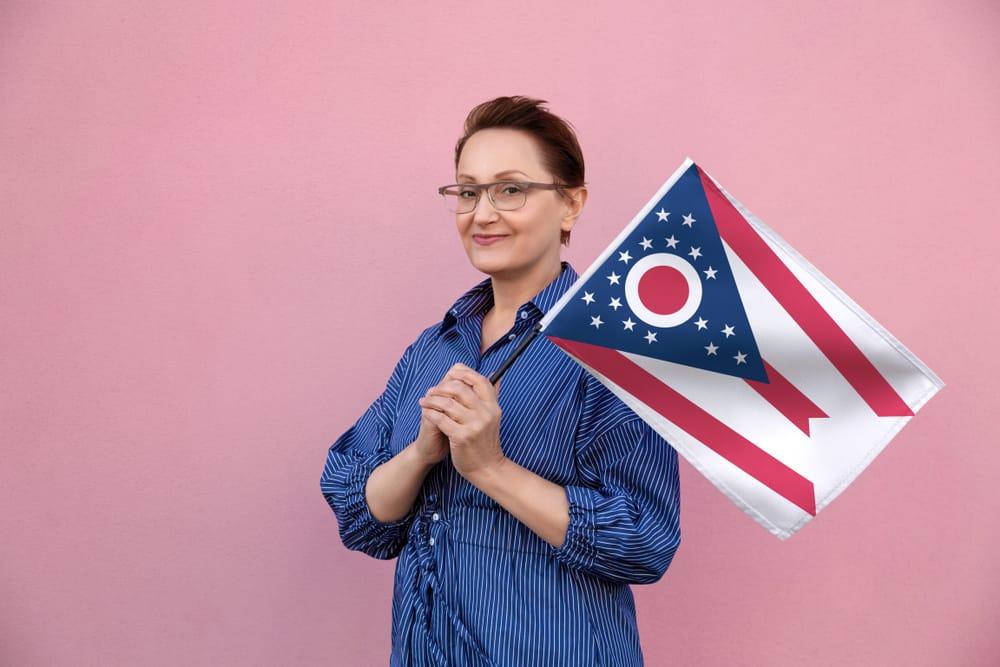 Lady holding Ohio flag with pink background