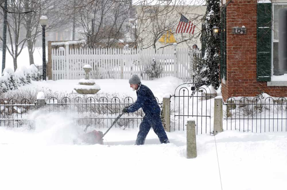 Man using a snow blower to remove snow from his driveway in winter.