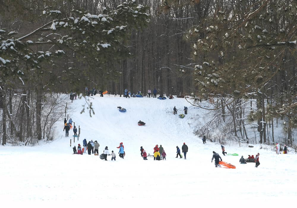 People sledding down a snowy hill in Solon, OH