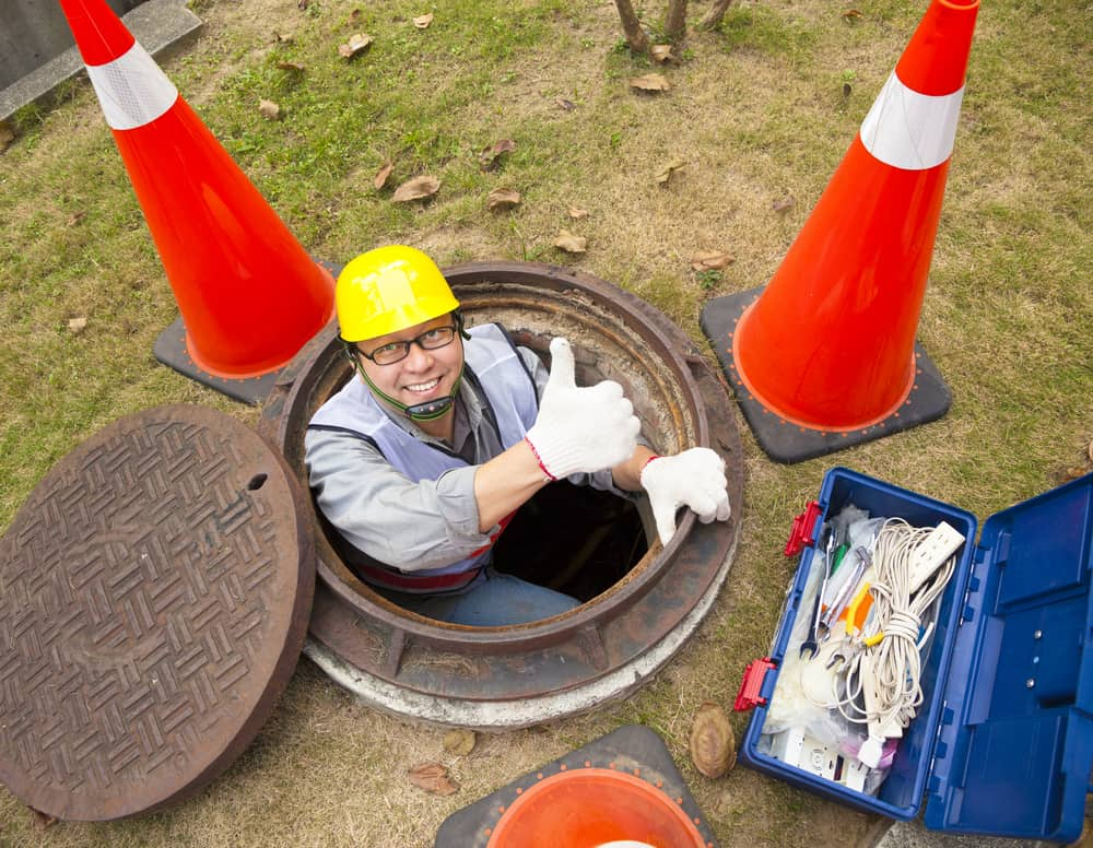 Happy sanitation worker in a manhole giving a thumbs-up.