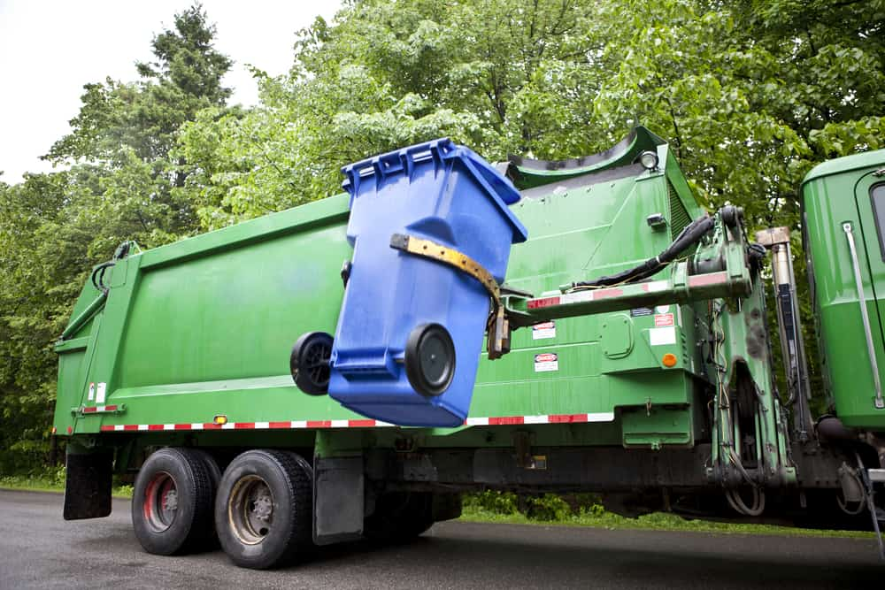Trash can being raised into a garbage truck by a mechanical arm.