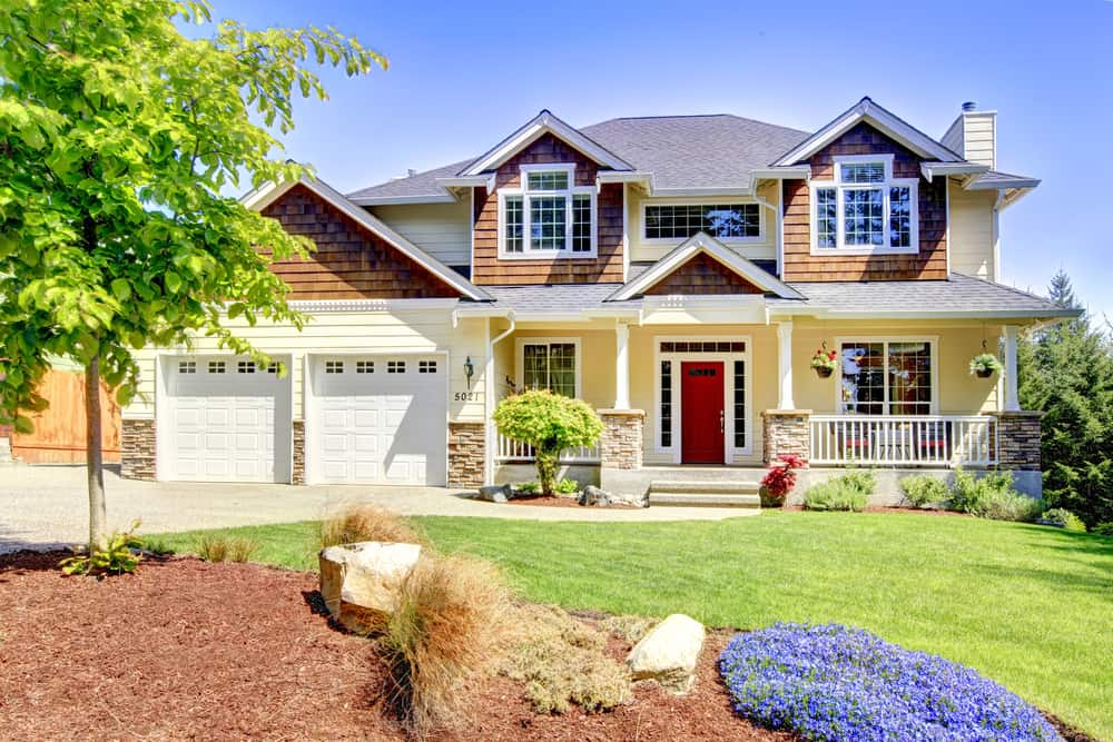 Large American beautiful house with a red door and two white garage doors.