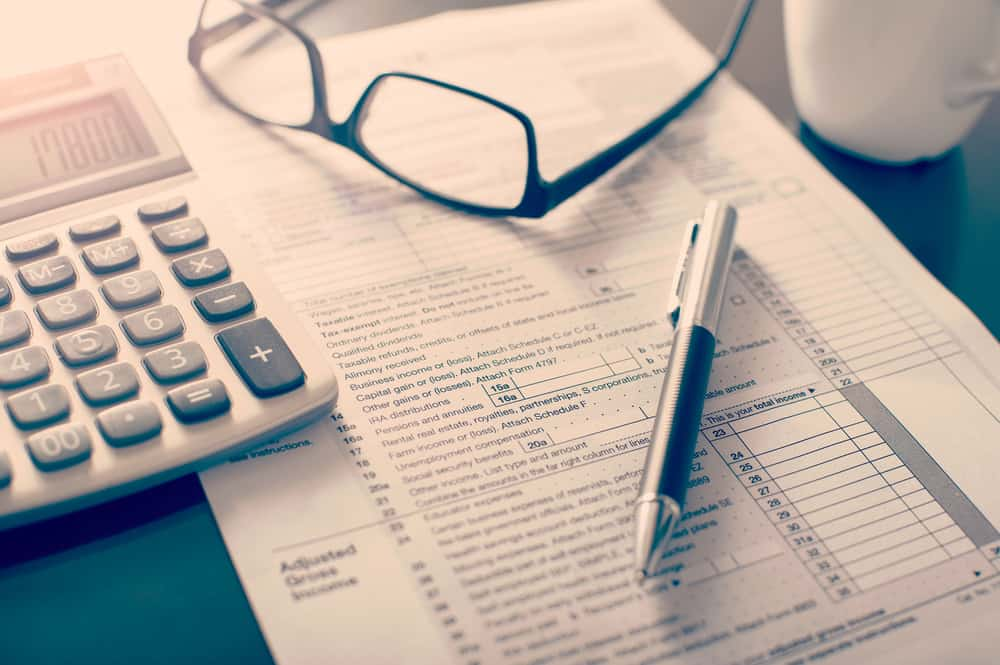 Pen, calculator, and forms for taxes.